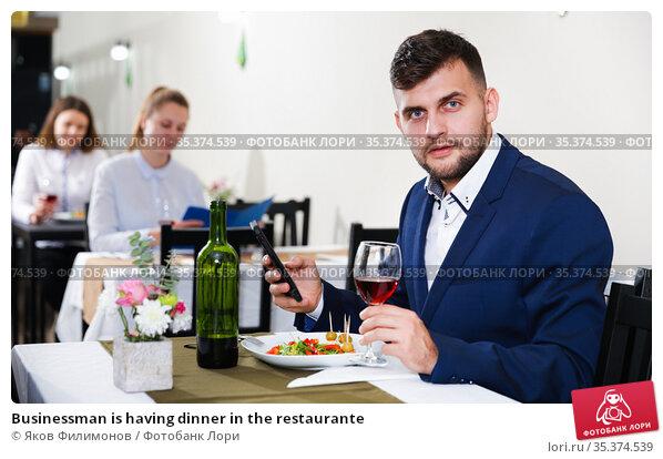Businessman is having dinner in the restaurante. Стоковое фото, фотограф Яков Филимонов / Фотобанк Лори
