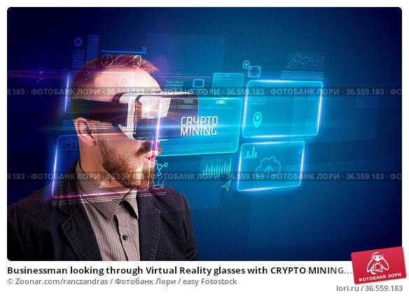 Businessman looking through Virtual Reality glasses with CRYPTO MINING... Стоковое фото, фотограф Zoonar.com/ranczandras / easy Fotostock / Фотобанк Лори