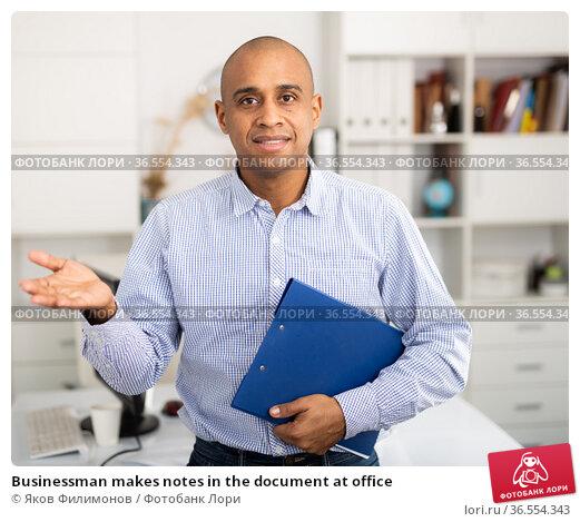 Businessman makes notes in the document at office. Стоковое фото, фотограф Яков Филимонов / Фотобанк Лори