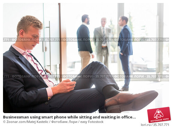 Businessman using smart phone while sitting and waiting in office... Стоковое фото, фотограф Zoonar.com/Matej Kastelic / easy Fotostock / Фотобанк Лори