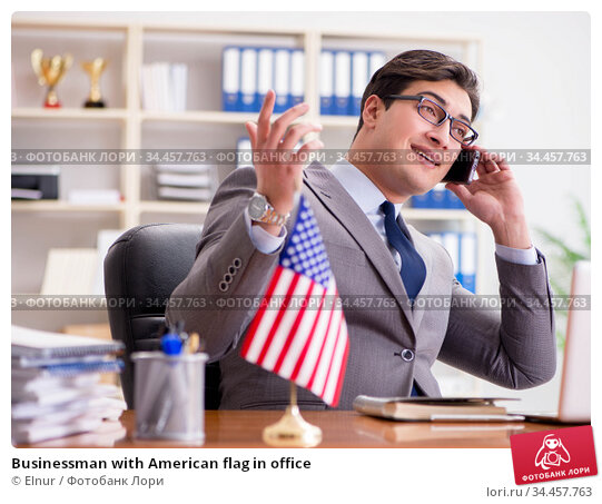 Businessman with American flag in office. Стоковое фото, фотограф Elnur / Фотобанк Лори