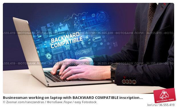 Businessman working on laptop with BACKWARD COMPATIBLE inscription... Стоковое фото, фотограф Zoonar.com/ranczandras / easy Fotostock / Фотобанк Лори