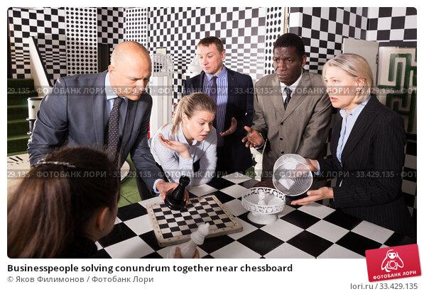 Купить «Businesspeople solving conundrum together near chessboard», фото № 33429135, снято 29 января 2019 г. (c) Яков Филимонов / Фотобанк Лори