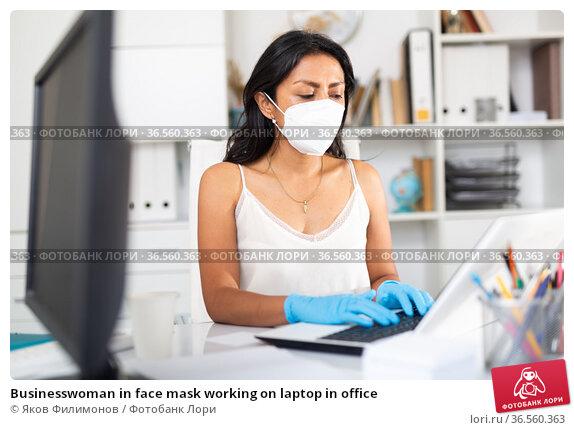 Businesswoman in face mask working on laptop in office. Стоковое фото, фотограф Яков Филимонов / Фотобанк Лори