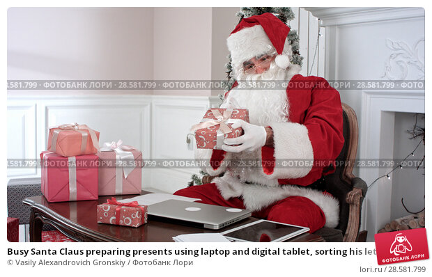 Купить «Busy Santa Claus preparing presents using laptop and digital tablet, sorting his letters and receiving a gift from a little girl», фото № 28581799, снято 21 июня 2018 г. (c) Vasily Alexandrovich Gronskiy / Фотобанк Лори