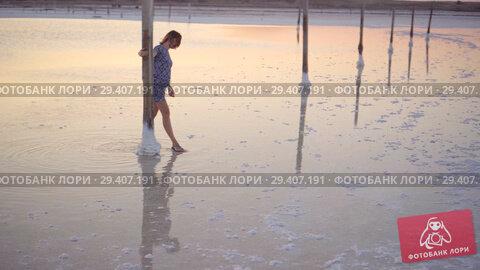 Купить «Calm girl enjoying sun, walking slowly through the water of a salt lake», видеоролик № 29407191, снято 3 ноября 2018 г. (c) Ирина Мойсеева / Фотобанк Лори