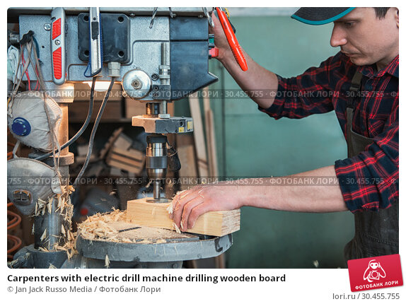 Carpenters with electric drill machine drilling wooden board. Стоковое фото, фотограф Jan Jack Russo Media / Фотобанк Лори