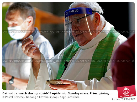 Catholic church during covid-19 epidemic. Sunday mass. Priest giving... Стоковое фото, фотограф Pascal Deloche / Godong / age Fotostock / Фотобанк Лори