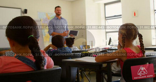 Купить «Caucasian male schoolteacher using digital tablet while teaching in classroom 4k», видеоролик № 31882443, снято 10 ноября 2018 г. (c) Wavebreak Media / Фотобанк Лори