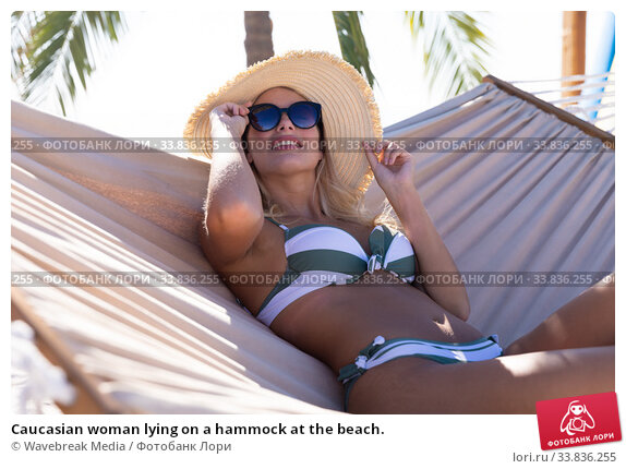 Купить «Caucasian woman lying on a hammock at the beach.», фото № 33836255, снято 25 февраля 2020 г. (c) Wavebreak Media / Фотобанк Лори