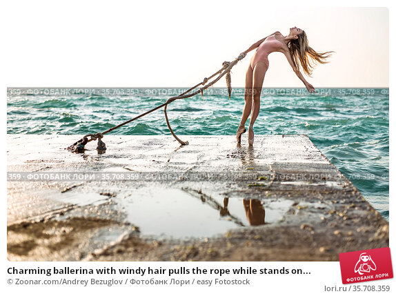Charming ballerina with windy hair pulls the rope while stands on... Стоковое фото, фотограф Zoonar.com/Andrey Bezuglov / easy Fotostock / Фотобанк Лори