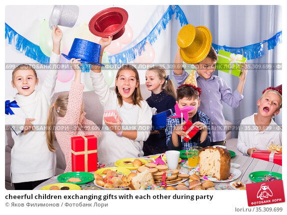 cheerful children exchanging gifts with each other during party. Стоковое фото, фотограф Яков Филимонов / Фотобанк Лори
