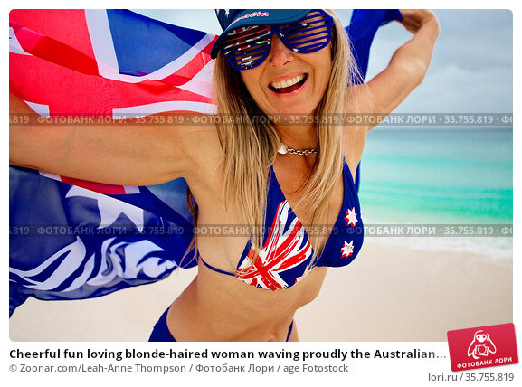 Cheerful fun loving blonde-haired woman waving proudly the Australian... Стоковое фото, фотограф Zoonar.com/Leah-Anne Thompson / age Fotostock / Фотобанк Лори
