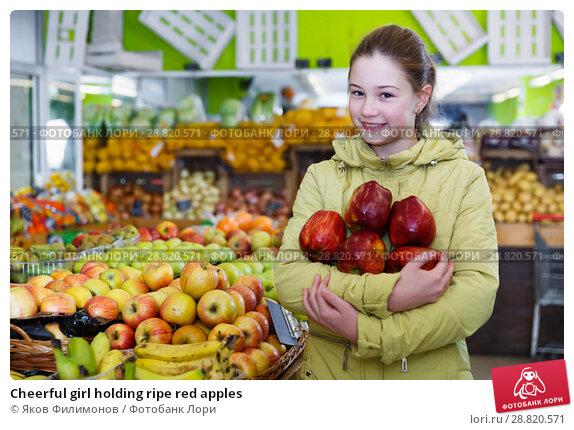 Купить «Cheerful girl holding ripe red apples», фото № 28820571, снято 13 февраля 2018 г. (c) Яков Филимонов / Фотобанк Лори