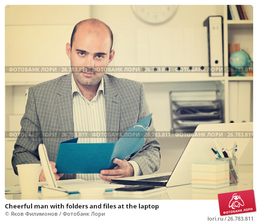 Купить «Cheerful man with folders and files at the laptop», фото № 26783811, снято 3 мая 2017 г. (c) Яков Филимонов / Фотобанк Лори