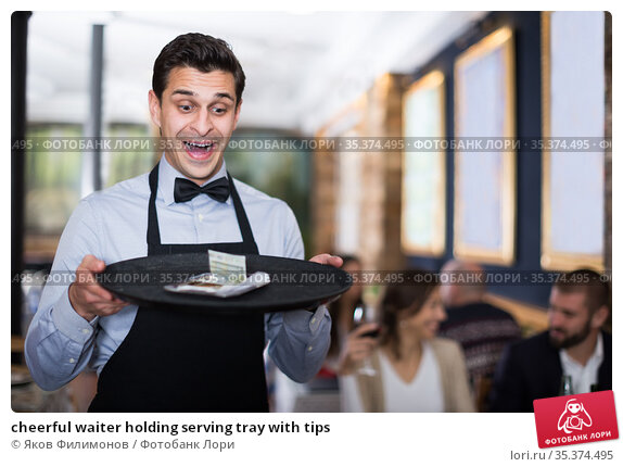 cheerful waiter holding serving tray with tips. Стоковое фото, фотограф Яков Филимонов / Фотобанк Лори
