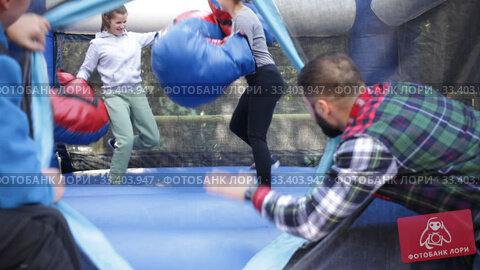 Купить «Cheerful women in big boxing gloves boxing on inflatable ring in outdoor amusement park», видеоролик № 33403947, снято 12 ноября 2019 г. (c) Яков Филимонов / Фотобанк Лори