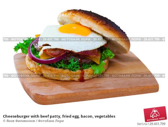 Купить «Cheeseburger with beef patty, fried egg, bacon, vegetables», фото № 29431799, снято 20 апреля 2019 г. (c) Яков Филимонов / Фотобанк Лори