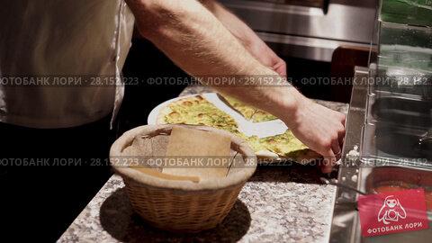 Купить «Chef cuts the ready focacci and puts it into the thatch basket», видеоролик № 28152223, снято 23 февраля 2018 г. (c) Ирина Мойсеева / Фотобанк Лори