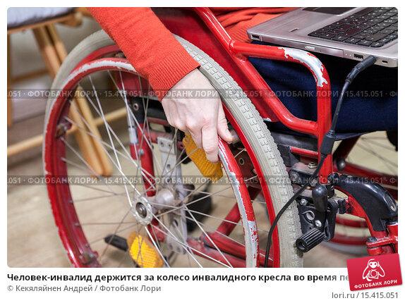 Купить «Человек-инвалид держится за колесо инвалидного кресла во время перемещения по офису с ноутбуком на коленях», фото № 15415051, снято 4 декабря 2015 г. (c) Кекяляйнен Андрей / Фотобанк Лори