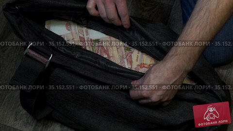 Человек открывает и проверяет сумку с наличными деньгами. Стоковое видео, видеограф Sergei Gorin / Фотобанк Лори
