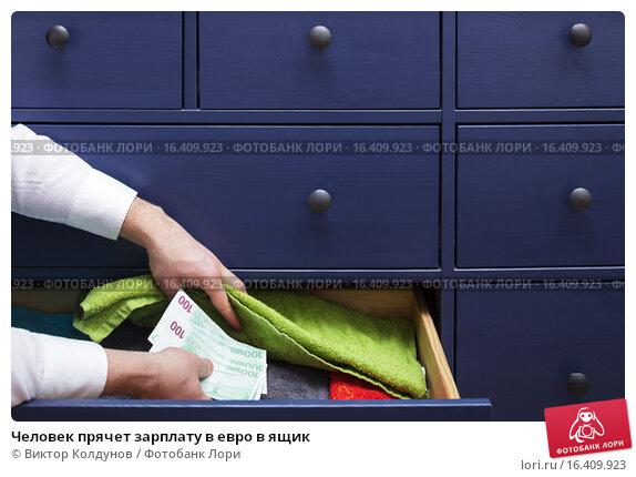 Человек прячет зарплату в евро в ящик. Стоковое фото, фотограф Виктор Колдунов / Фотобанк Лори