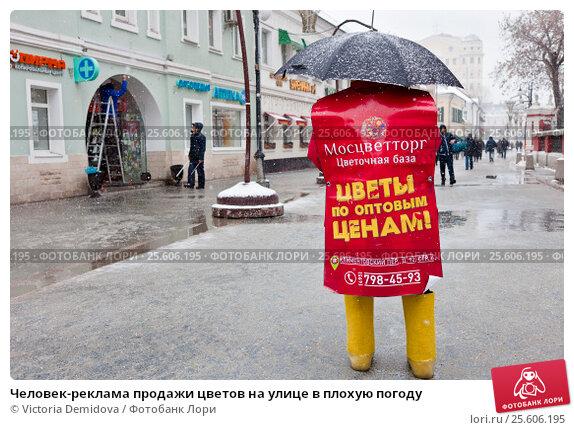 Купить «Человек-реклама продажи цветов на улице в плохую погоду», фото № 25606195, снято 23 февраля 2017 г. (c) Victoria Demidova / Фотобанк Лори
