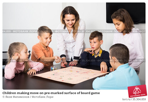 Children making move on pre-marked surface of board game. Стоковое фото, фотограф Яков Филимонов / Фотобанк Лори