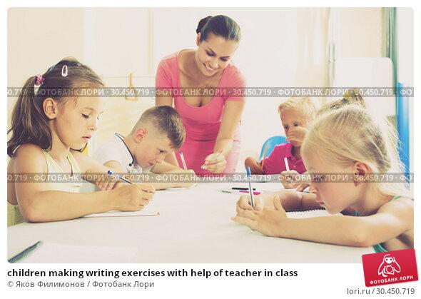 children making writing exercises with help of teacher in class. Стоковое фото, фотограф Яков Филимонов / Фотобанк Лори