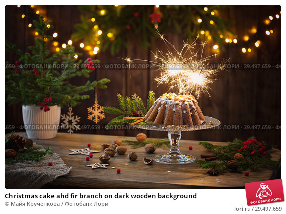 Купить «Christmas cake ahd fir branch on dark wooden background», фото № 29497659, снято 25 ноября 2018 г. (c) Майя Крученкова / Фотобанк Лори