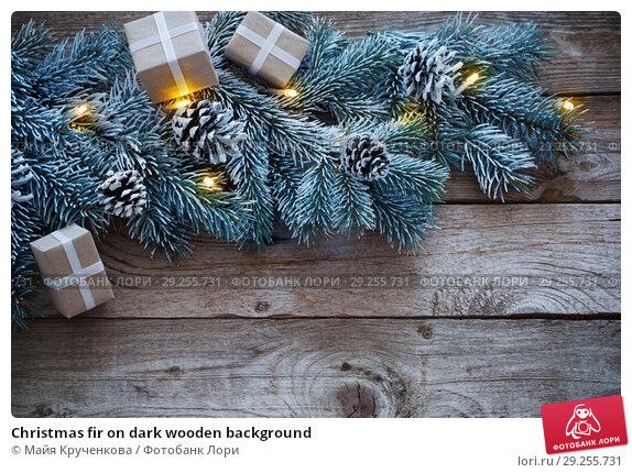 Купить «Christmas fir on dark wooden background», фото № 29255731, снято 15 октября 2018 г. (c) Майя Крученкова / Фотобанк Лори