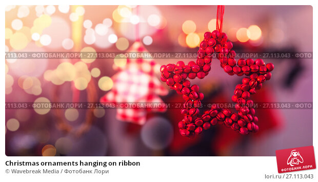 Купить «Christmas ornaments hanging on ribbon», фото № 27113043, снято 22 ноября 2017 г. (c) Wavebreak Media / Фотобанк Лори