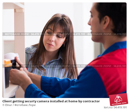 Client getting securty camera installed at home by contractor. Стоковое фото, фотограф Elnur / Фотобанк Лори