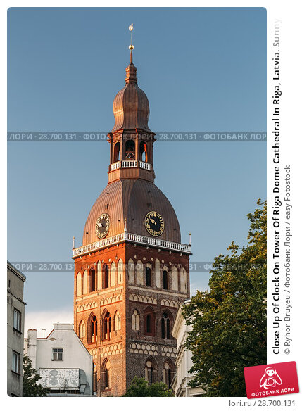 Купить «Close Up Of Clock On Tower Of Riga Dome Cathedral In Riga, Latvia. Sunny Blue Sky Background. Belfry Bell Tower In Golden Hour At Sunset Or Sunrise Time.», фото № 28700131, снято 1 июля 2016 г. (c) easy Fotostock / Фотобанк Лори