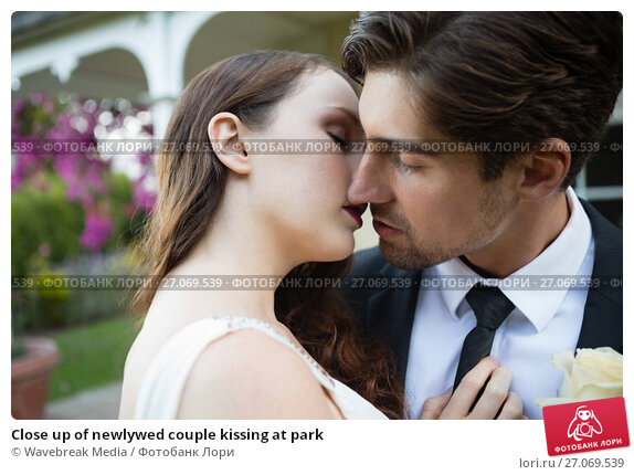 Купить «Close up of newlywed couple kissing at park», фото № 27069539, снято 2 мая 2017 г. (c) Wavebreak Media / Фотобанк Лори