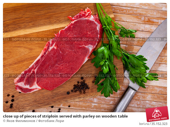 close up of pieces of striploin served with parley on wooden table. Стоковое фото, фотограф Яков Филимонов / Фотобанк Лори