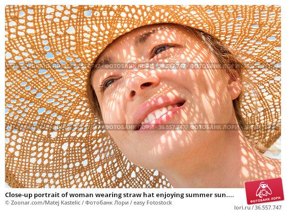 Close-up portrait of woman wearing straw hat enjoying summer sun.... Стоковое фото, фотограф Zoonar.com/Matej Kastelic / easy Fotostock / Фотобанк Лори