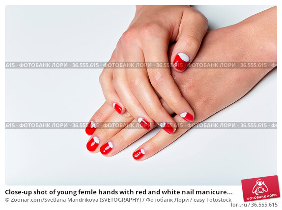 Close-up shot of young femle hands with red and white nail manicure... Стоковое фото, фотограф Zoonar.com/Svetlana Mandrikova (SVETOGRAPHY) / easy Fotostock / Фотобанк Лори
