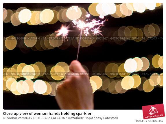 Close up view of woman hands holding sparkler. Стоковое фото, фотограф Zoonar.com/DAVID HERRAEZ CALZADA / easy Fotostock / Фотобанк Лори