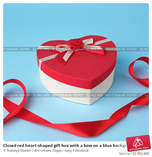 Closed red heart-shaped gift box with a bow on a blue background, top view, festive backdrop. Valentine gift. Стоковое фото, фотограф Natalya Danko / easy Fotostock / Фотобанк Лори
