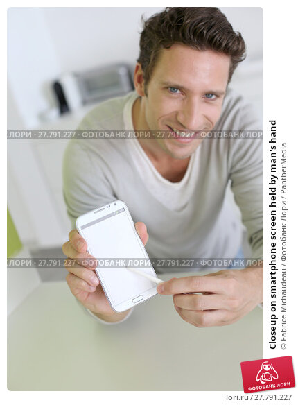 Купить «Closeup on smartphone screen held by man's hand», фото № 27791227, снято 18 февраля 2018 г. (c) PantherMedia / Фотобанк Лори
