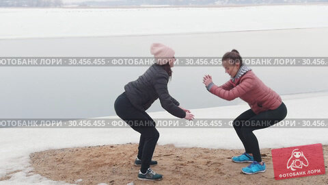 Cold weather. Two slim women in jackets doing squats on the snowy beach. Стоковое видео, видеограф Константин Шишкин / Фотобанк Лори