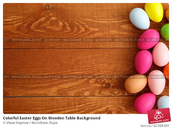 Купить «Colorful Easter Eggs On Wooden Table Background», фото № 32934931, снято 25 марта 2019 г. (c) Иван Карпов / Фотобанк Лори