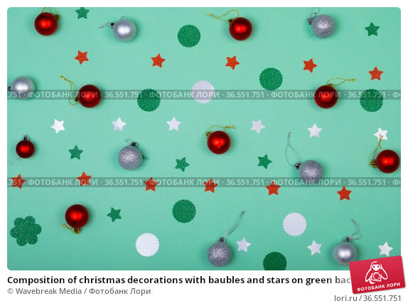Composition of christmas decorations with baubles and stars on green background. Стоковое фото, агентство Wavebreak Media / Фотобанк Лори