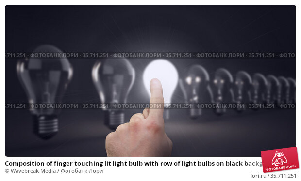 Composition of finger touching lit light bulb with row of light bulbs on black background. Стоковое фото, агентство Wavebreak Media / Фотобанк Лори