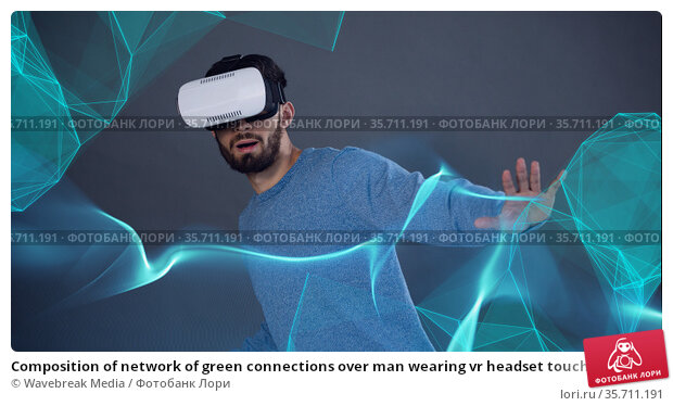 Composition of network of green connections over man wearing vr headset touching screen. Стоковое фото, агентство Wavebreak Media / Фотобанк Лори