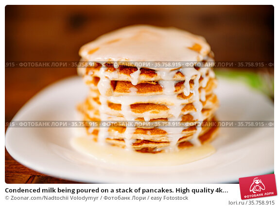 Condenced milk being poured on a stack of pancakes. High quality 4k... Стоковое фото, фотограф Zoonar.com/Nadtochii Volodymyr / easy Fotostock / Фотобанк Лори