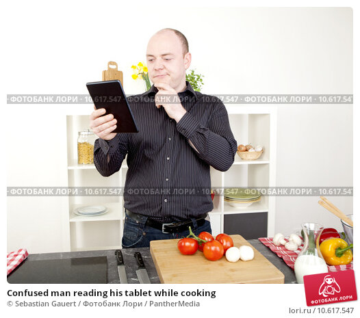 Confused man reading his tablet while cooking. Стоковое фото, фотограф Sebastian Gauert / PantherMedia / Фотобанк Лори