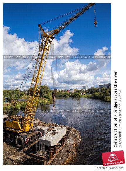 Купить «Construction of a bridge across the river», фото № 29043703, снято 28 августа 2015 г. (c) Евгений Ткачёв / Фотобанк Лори