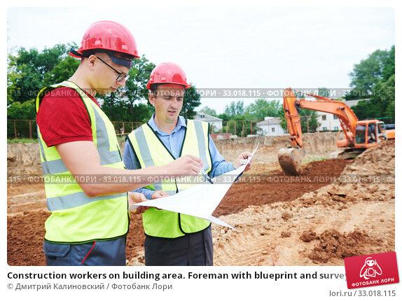 Купить «Construction workers on building area. Foreman with blueprint and surveyoor», фото № 33018115, снято 21 июня 2018 г. (c) Дмитрий Калиновский / Фотобанк Лори
